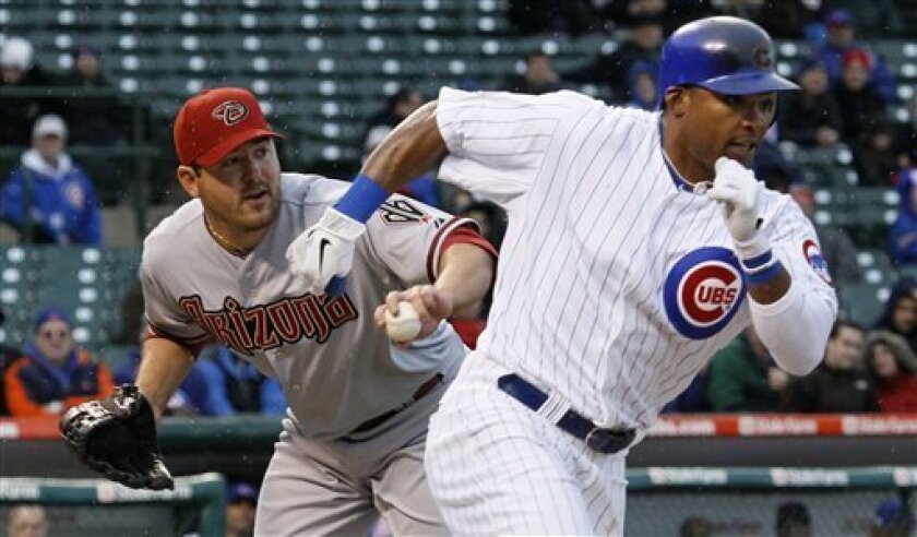 Chicago Cubs' Marlon Byrd, right, runs safely to first as the throw from Arizona Diamondbacks pitcher Joe Saunders, left, pulls first baseman Russell Branyan off the bag, during the fourth inning of a baseball game Monday, April 4, 2011 in Chicago. Byrd would later score. (AP Photo/Charles Rex Arbogast)