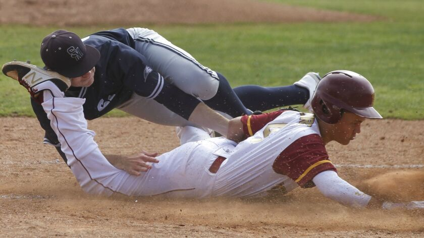 Torrey Pines' Ty McGuire (right) is tagged out at home plate by San Marcos pitcher Shane Whittaker in the first inning Friday. The Knights defeated the Falcons 10-5 in North County Tournament play.