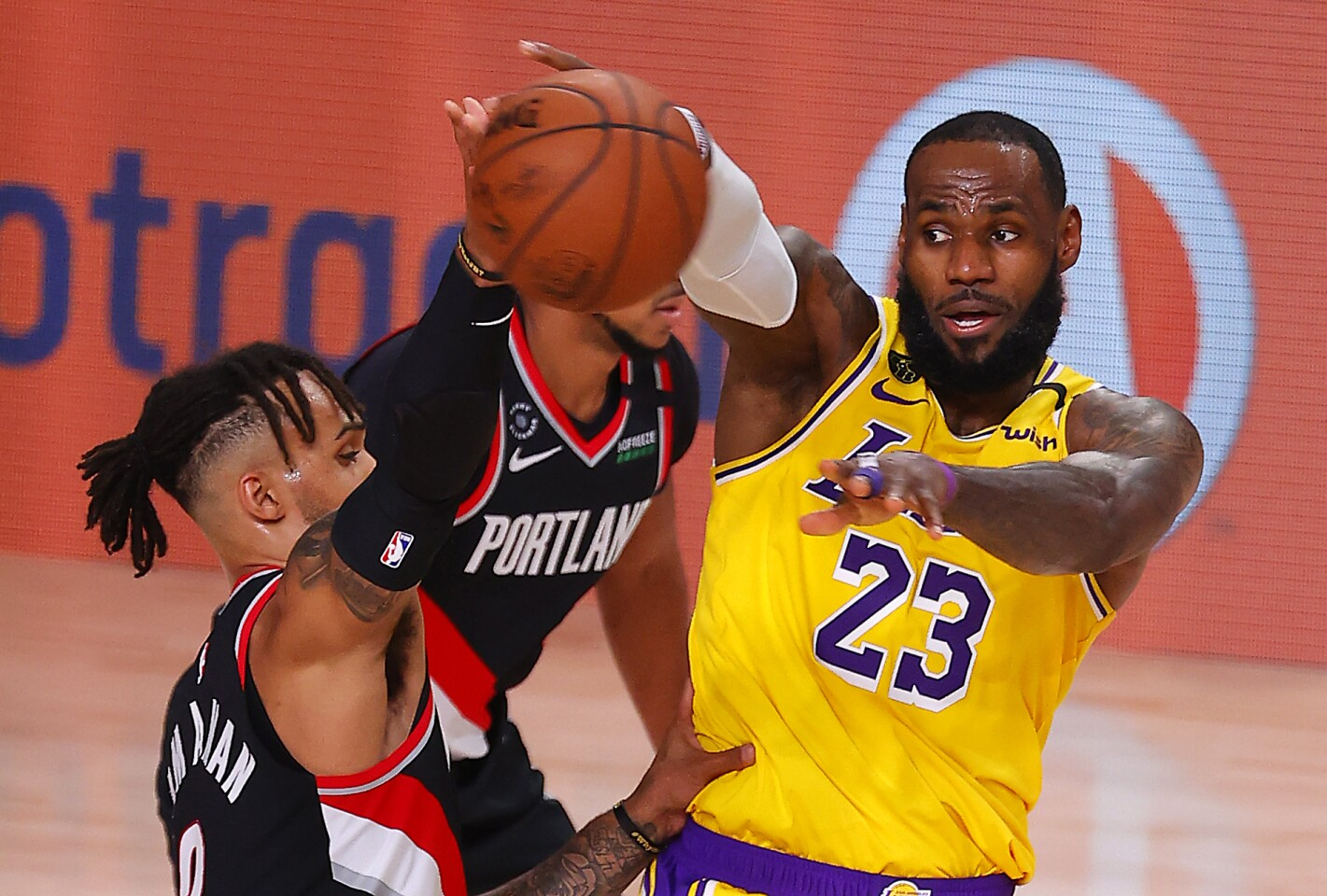Lakers forward LeBron James tries to pass around Portland's Gary Trent Jr. during the first half.