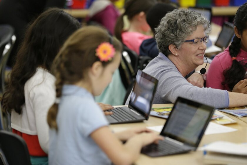 In this Thursday, March 12, 2015 photo, teacher Debbie Cruger-Hansen assists fourth graders using Google docs to complete an exercise at Mira Vista School in Richmond, Calif. Schools around the country are teaching students as young as 6 years old, basic typing and other keyboarding skills. The Com