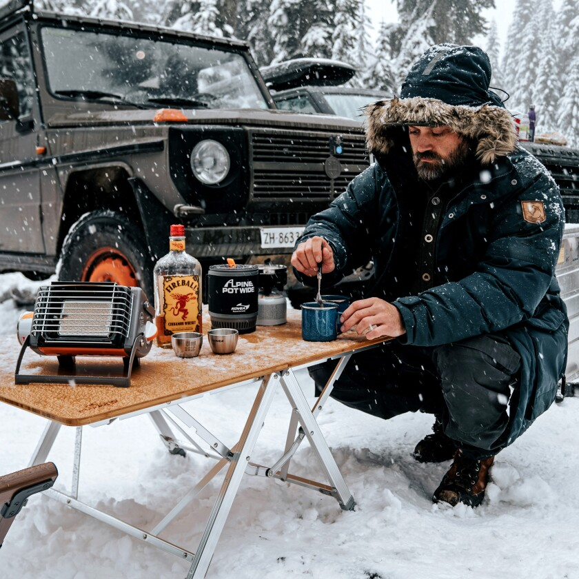 A man in the snow having a drink with his overland vehicle in the background.