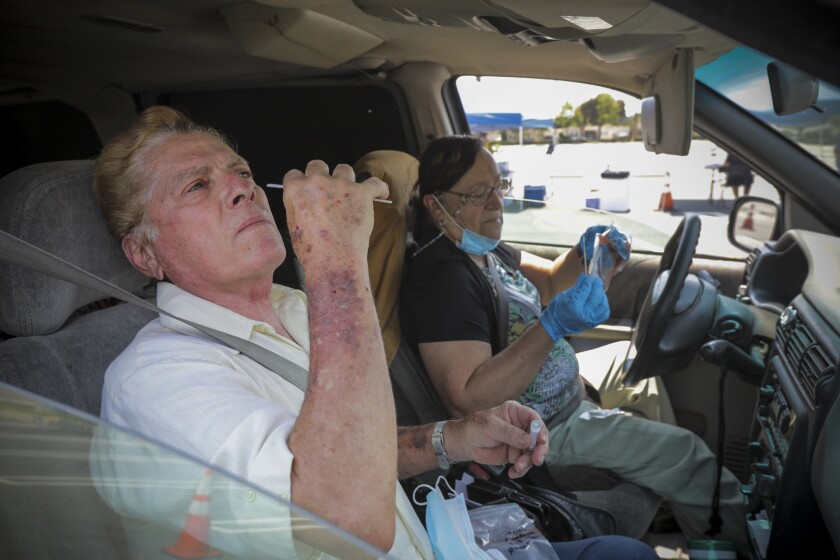 Daniel  and Linda Mendoza take COVID-19 tests at a drive-in site in Santa Ana.