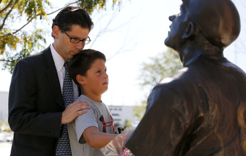 Joshua Raymond, left, holds his son, Max Raymond, 9, while paying their respects at a statue of former New York Yankees hall of fame catcher Yogi Berra outside of the Yogi Berra Museum, Wednesday, Sept. 23, 2015, in Little Falls, N.J. Berra died Tuesday at the age of 90. (AP Photo/Julio Cortez)