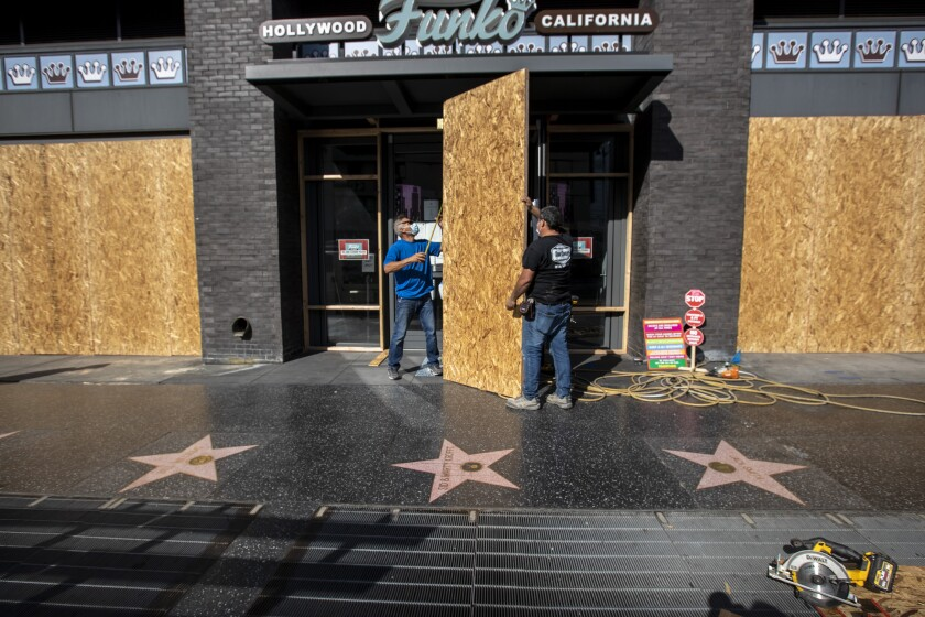 Two men boarding up a storefront on the Hollywood Walk of Fame