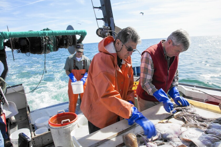 """Sens. Joe Manchin III (D-W.Va.), left, and Sheldon Whitehouse (D-R.I.) off the coast of Point Judith, R.I. """"There is no doubt that 7 billion people have impacted our world's climate,"""" Manchin said. """"We have a responsibility. But no one is going to stop using fossil [fuels] for a long time."""""""