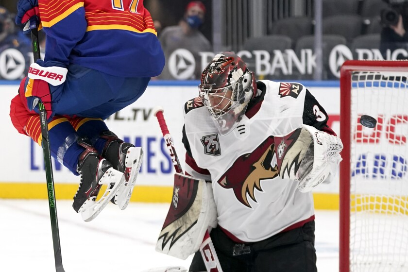 A puck is deflected by Arizona Coyotes goaltender Antti Raanta, right, as St. Louis Blues' Jaden Schwartz, left, leaps out of the way during the second period of an NHL hockey game Thursday, Feb. 4, 2021, in St. Louis. (AP Photo/Jeff Roberson)