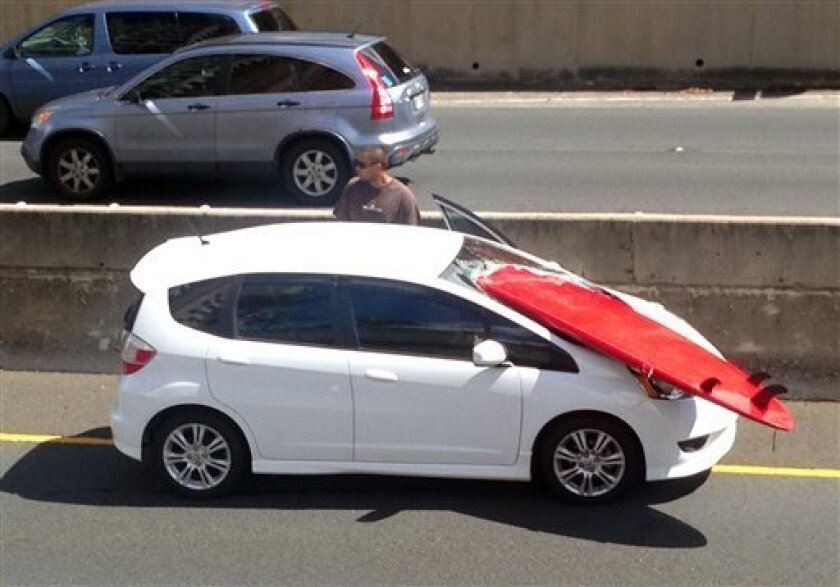 In this image provided by Donard Sonoda, an unidentified man stops to assist driver Jerrin Ching (not seen) after a surfboard smashed through the front windshield of his car on a freeway in Honolulu, Sunday, Sept. 1, 2013. Witnesses said they saw the surfboard fall from an overpass and hit Ching's car as he was driving in the far left lane. Ching suffered only minor scratches in the incident. (AP Photo/Courtesy of Donard Sonoda)