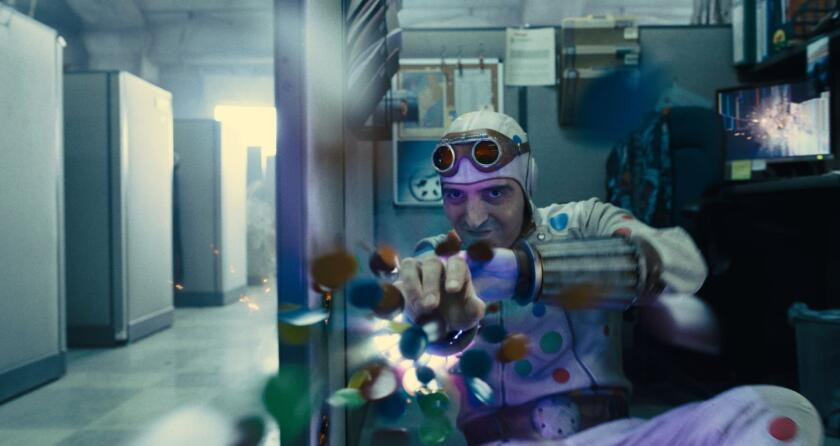 David Dastmalchian as Polka-Dot Man crouches and fires blobs from a weapon on his forearm.