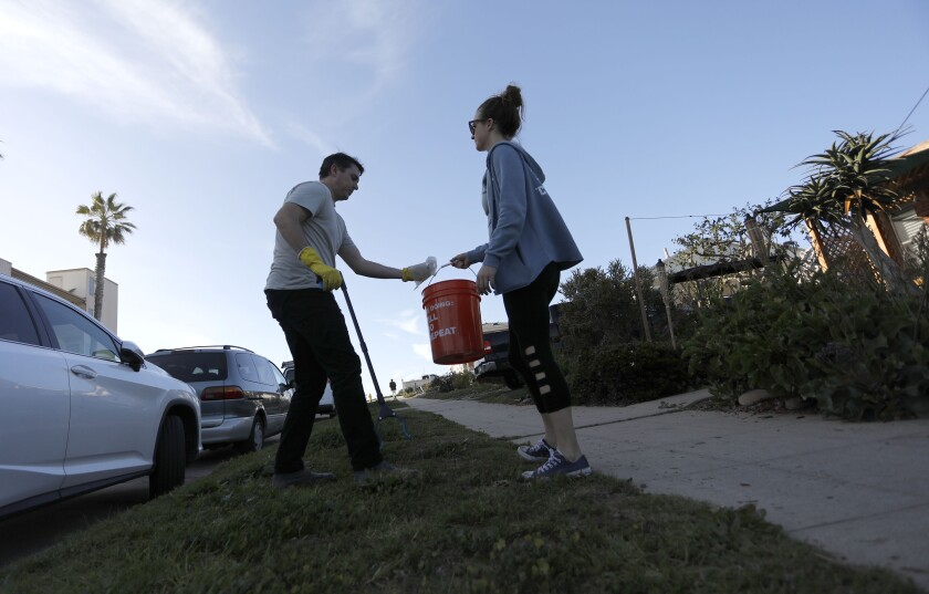 """Aaron Null, left, and Laura Price pick up trash they find on walks around their Sunset Cliffs neighborhood in Ocean Beach. Null created a Facebook group in July where residents """"adopt"""" a street and commit to picking up trash once a week. The group has expanded to other beach communities and most recently to North Park."""