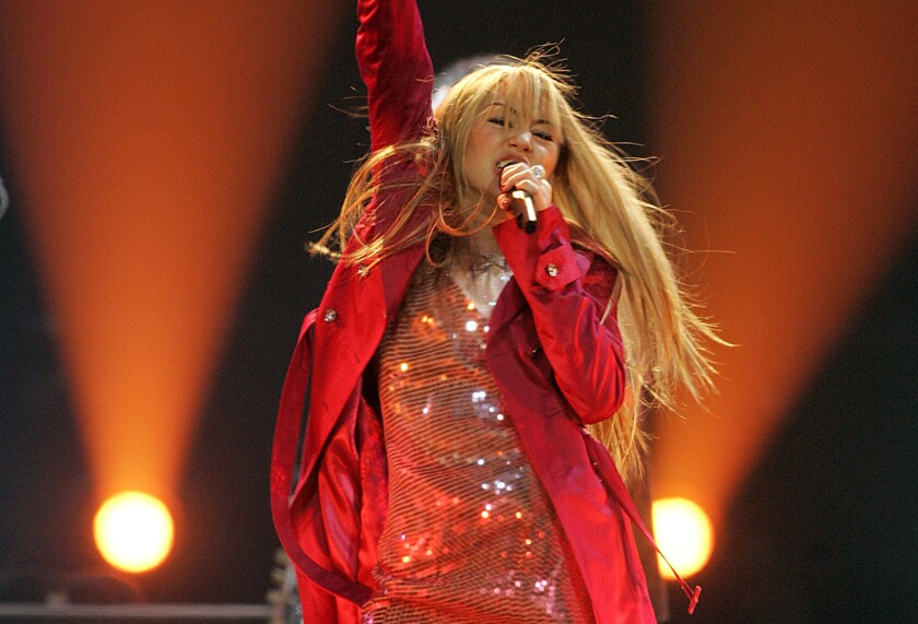 Miley Cyrus, dressed as Hannah Montana, raising a fist in the air and singing into a microphone