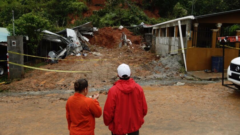 Panamanian civil defense workers view a mudslide that destroyed a home and killed the couple inside in Arraijan, on the outskirts of Panama City on Tuesday.