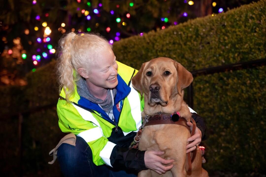 Kym Crosby et le chien-guide Tron posent devant les lumières de Noël.