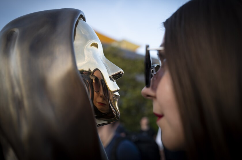 A woman looks at her reflection in a newly unveiled statue of the mysterious developer of the Bitcoin digital currency in Budapest, Hungary, Thursday, Sept. 16, 2021. A bronze statue was unveiled in Hungary's capital on Thursday which its creators say is the first in the world to pay homage to the anonymous creator of the Bitcoin digital currency. Erected in a business park near the Danube River in Budapest, the bust sits atop a stone plinth engraved with the name of Satoshi Nakamoto, the pseudonym of the mysterious developer of Bitcoin whose true identity is unknown. (AP Photo/Bela Szandelszky)