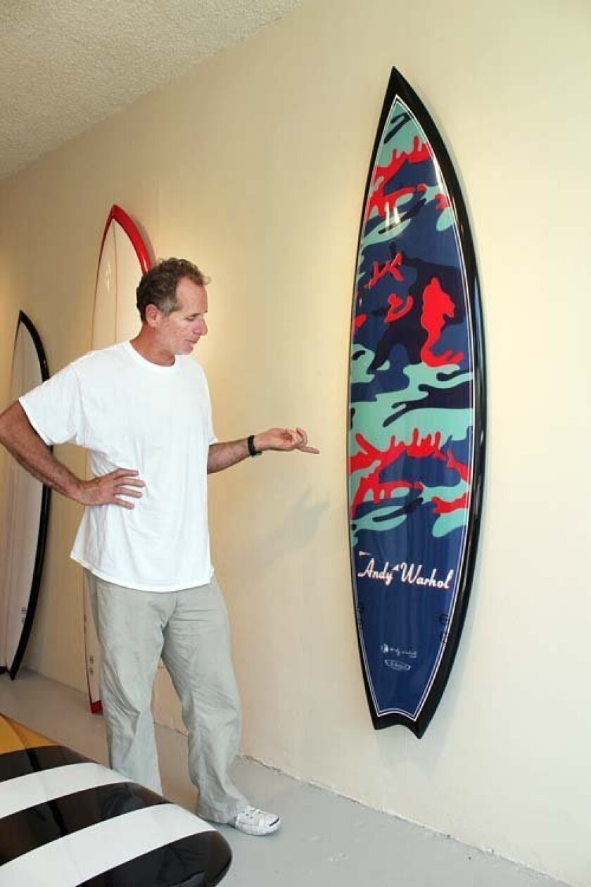 La Jolla surfboard shaper Tim Bessell displays one of the 7-foot, 4-inch magic-style surfboards he created from one of Andy Warhol's camouflage designs.