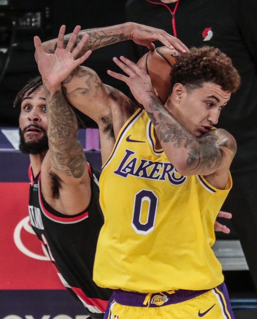 Lakers forward Kyle Kuzma wrestles to control the ball while being harassed by Portland Trail Blazers guard Gary Trent Jr.