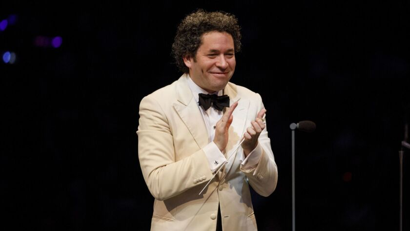 Conductor Gustavo Dudamel applauds during the LA Philharmonic 100th anniversary concert at the Holly