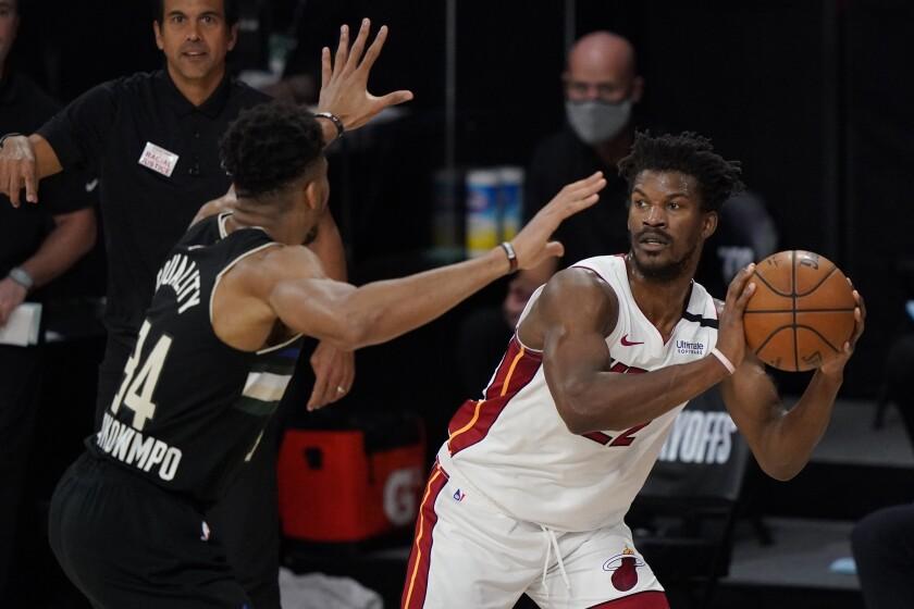 Miami Heat's Jimmy Butler, right, looks to pass around Milwaukee Bucks' Giannis Antetokounmpo.