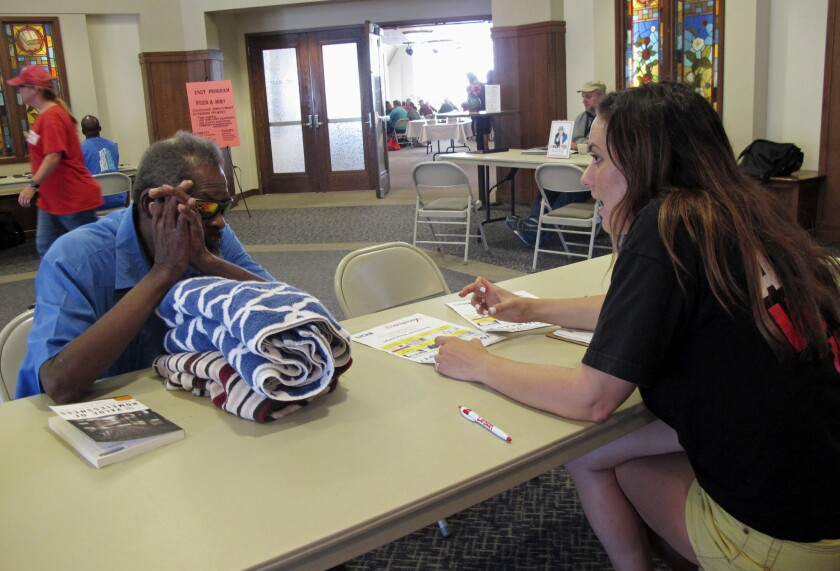 In this Aug., 31, 2016, photo, Molly McGrath, who works for VoteRiders to help people get the required photo identification needed to vote, assists Mike Battles with questions about early voting in Madison, Wis, McGrath is helping explain Wisconsin's complex and seemingly ever-changing election laws to voters.