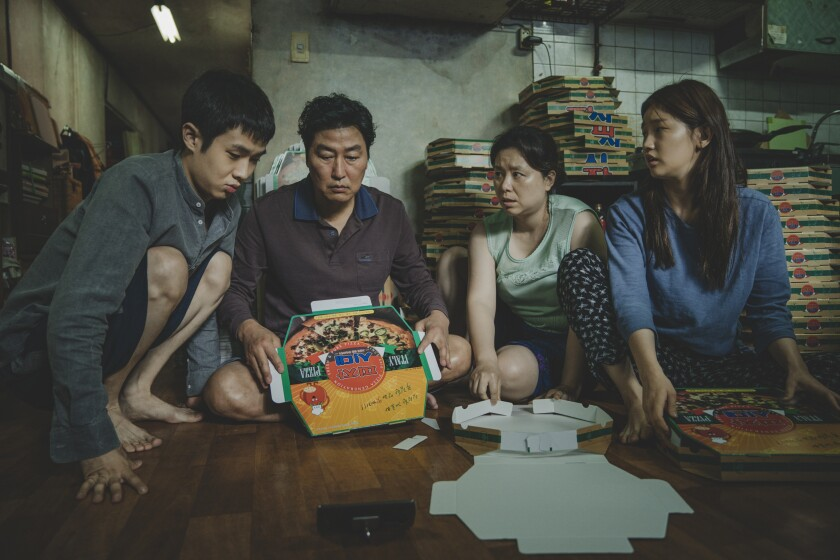 "The Kim family folds pizza boxes in Bong Joon Ho's ""Parasite."""