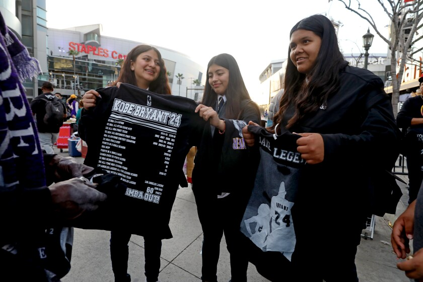 Bridgette Portillo, 13, from left; Martha Martinez, 14; and Elizabeth Hernandez, 12, hold Kobe Bryant memorial T-shirts from a vendor outside Staples Center.