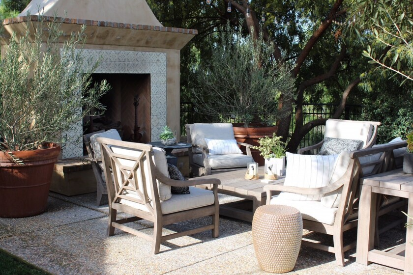 An outside room is ribboned with serene neutrals and features patterned fireplace tiles that are com