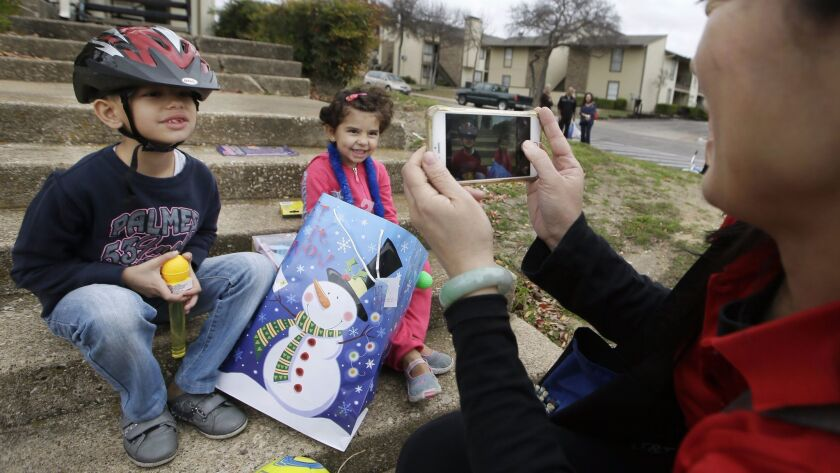 Volunteer Jessica Yang takes a photo of newly arrived Syrian refugee siblings Majerid, 7, left, and Jory, 4, after presenting them with gifts outside their family's apartment in Dallas in 2015.