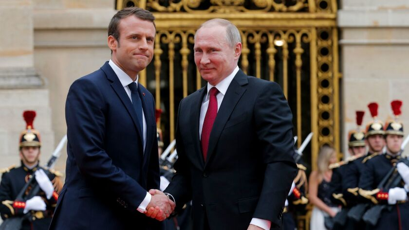Russian President Vladimir Putin, right, is welcomed by French President Emmanuel Macron at the Pala