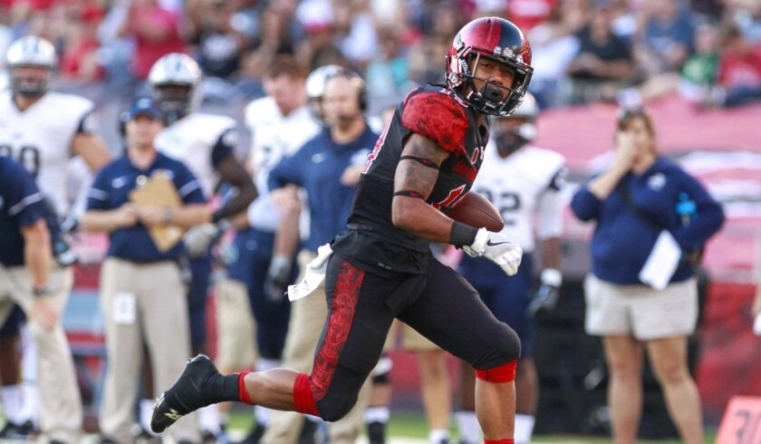 The Aztecs' D.J. Pumphrey runs for a touchdown in the first quarter.