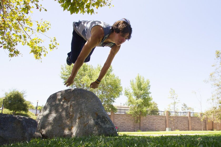 At a local park in Vista, Merrick Larsen runs through several leaps, jumps and tumbles during a typical training session in parkour.