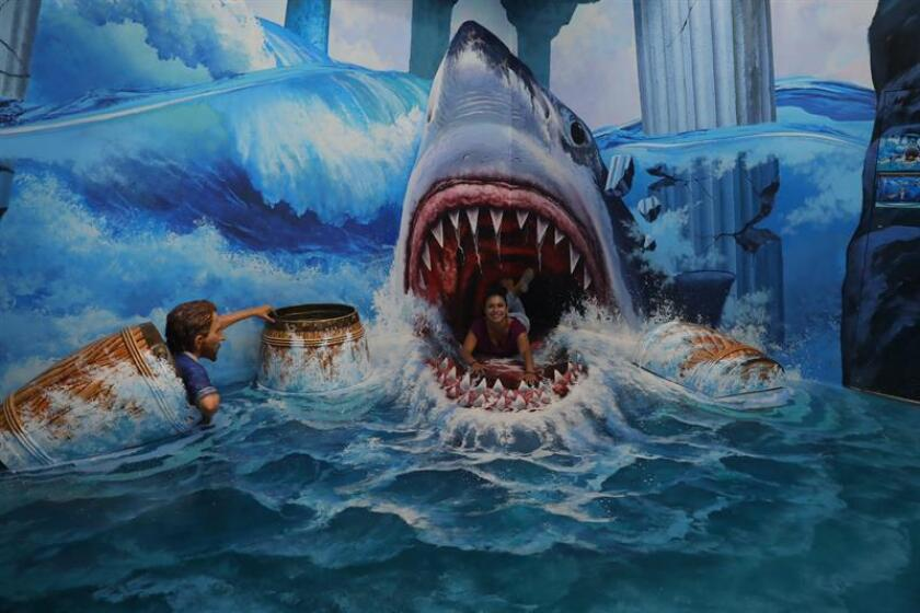 A woman seems eaten by a shark on Feb. 7, 2019, at Trick Eye, the museum in Mexico City that originated in South Korea and whose concept is based on augmented reality with larger-than-life visual effects. EFE-EPA/Sashenka Gutierrez
