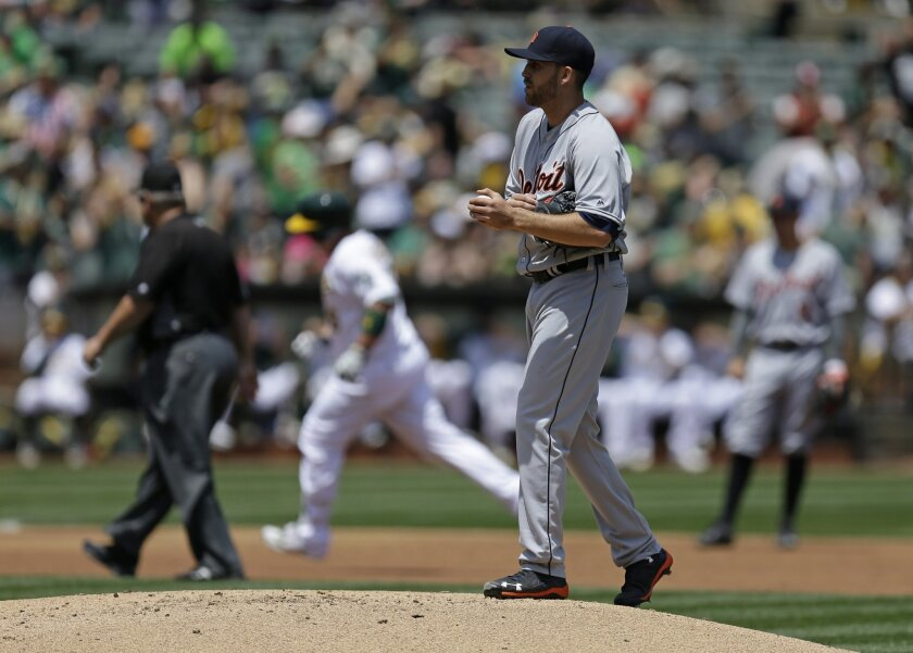 Detroit Tigers pitcher Matt Boyd, foreground, waits for Oakland Athletics' Billy Butler to run the bases after Butler hit a home run in the second inning of a baseball game Saturday, May 28, 2016, in Oakland, Calif. (AP Photo/Ben Margot)