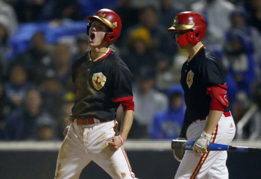 Orange Lutheran shortstop Justin DiCriscio, left, celebrates after scoring a run during a 2-0 victory over La Mirada at the Great Park Baseball Stadium in Irvine on Wednesday.