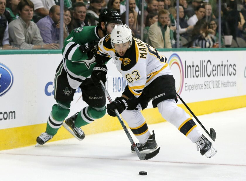 Boston Bruins left wing Brad Marchand (63) gains control of the puck in front of Dallas Stars' Jason Demers (4) during the second period of an NHL hockey game, Saturday, Feb. 20, 2016, in Dallas. (AP Photo/Tony Gutierrez)