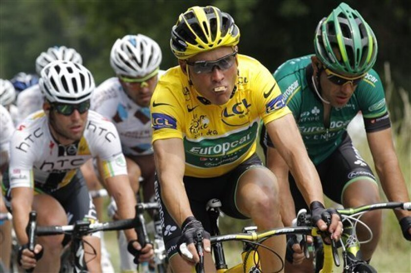 Thomas Voeckler of France, wearing the overall leader's yellow jersey, eats while riding in the pack with Mark Cavendish of Britain, left, during the 10th stage of the Tour de France cycling race over 158 kilometers (98.2 miles) starting in Aurillac and finishing in Carmaux, south central France, Tuesday July 12, 2011. (AP Photo/Christophe Ena)