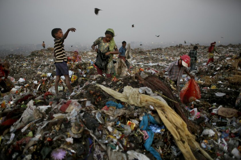 In this Oct. 17, 2014 photo, young waste pickers look for recyclable items at a landfill on the outskirts of New Delhi, India. Rag picking is effectively the primary recycling system in India. While the rag pickers offer invaluable services to the city, they have few rights and are exposed to deadly poisons everyday. (AP Photo/Altaf Qadri)
