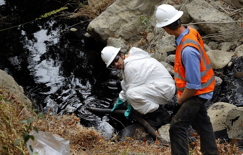A contractor guides a hose into Prince Barranca gorge in Ventura to pump out oil that spilled