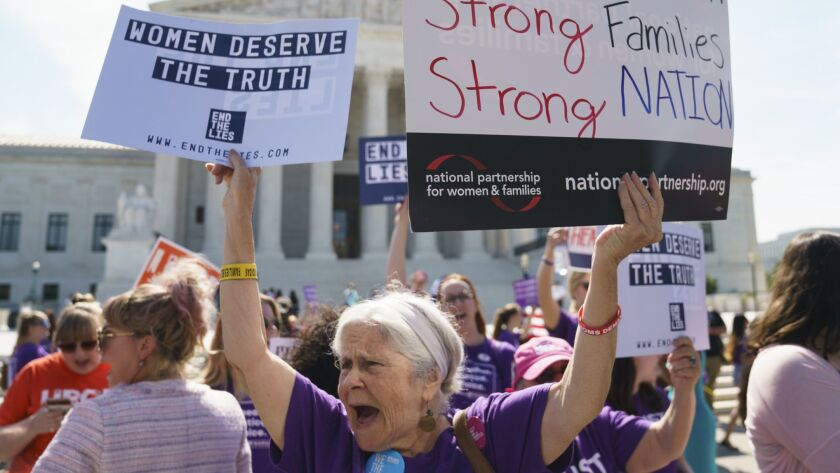 A woman protests outside the Supreme Court Building on Capitol Hill in in Washington, Tuesday, June