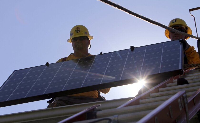 Lead installer for Sullivan Solar Power Mike DeCarl, right, and construction wireman Christopher Johnson grab hold of a solar panel that was hoisted up for installation on the roof of a home in Carlsbad in 2013.