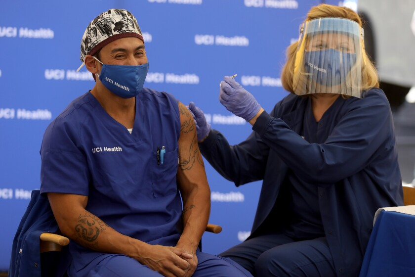 Erik Mara, a respiratory therapist at UCI Health, receives the COVID-19 vaccine Wednesday in Orange.