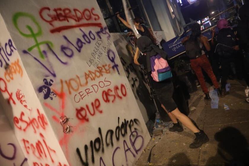 Manifestantes rompen vidrios de un edificio y escriben consignas durante una protesta en contra de abusos sexuales por parte de cuerpos policiales en Ciudad de México (México). EFE/Sashenka Gutiérrez