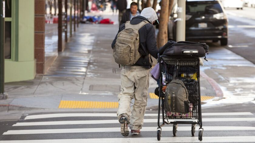 A homeless man with a grocery cart walks down a street in the Mission District on April 17 in San Francisco. The city is grappling with human waste on public streets stemming, in part, from the area's homeless population.