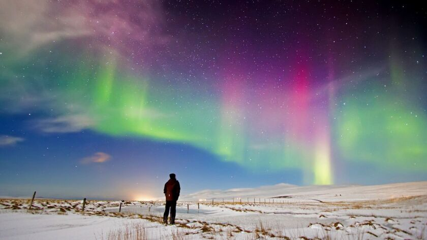 ICELAND: Looking at the Aurora Borealis in north Iceland with the snow covered ground and stars and