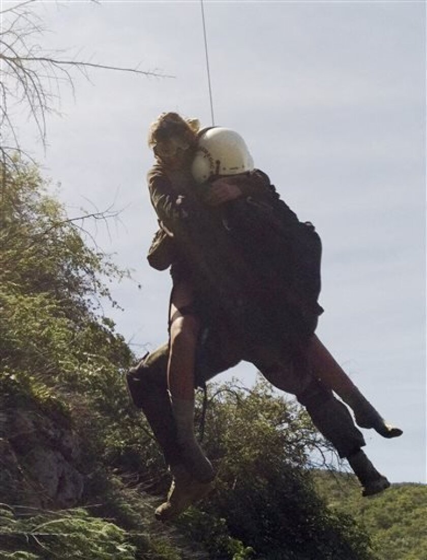 File-This April 4,2013 file photo provided by Los Angeles County Search and Rescue Reserve Deputy Doug Cramoline shows the helicopter rescue of Kyndall Jack, 18, by an L.A. County deputy after being missing for five days in rugged country near Rancho Santa Margarita, Calif. Authorities say two teen hikers lost for days in a California forest might have to pay for the search after a small amount of drugs was found in their car. (AP Photo/L.A. County Search and Rescue Reserve, Deputy Doug Cramolin