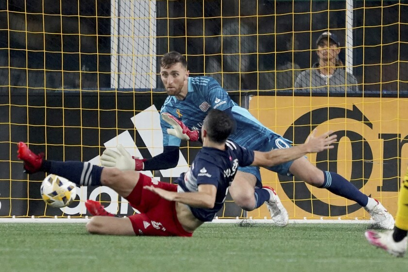 New England Revolution goalkeeper Matt Turner (30) makes a save as teammate Matt Polster slides past during the second half of a MLS soccer match against the Columbus Crew, Saturday, Sept. 18, 2021, in Foxborough, Mass. (AP Photo/Mary Schwalm)