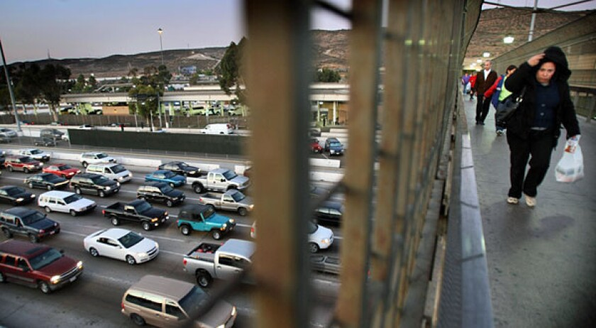 Traffic on I¿5 approaching the San Ysidro/Tijuana border gate clogs all southbound lanes. Shoppers and workers walk on an overpass leading to the pedestrian gate to Mexico.