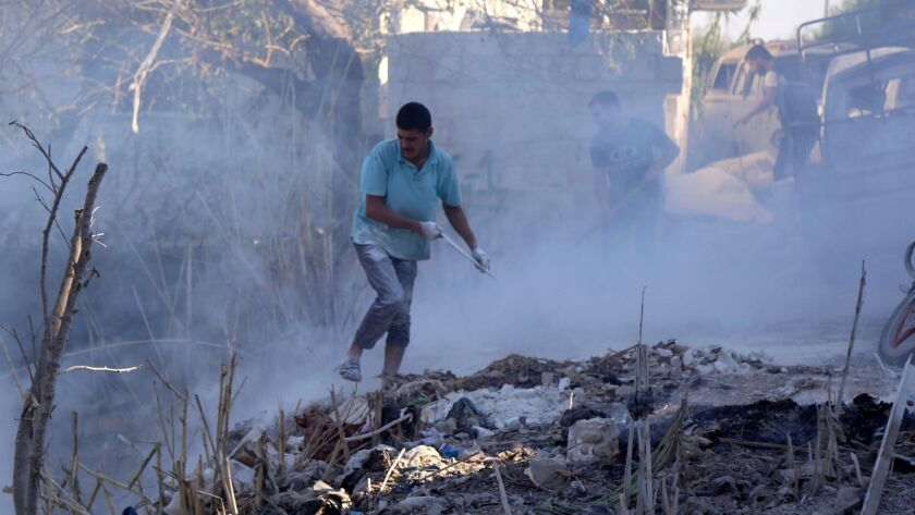 Syrians use dirt to put out a fire at the scene of a reported airstrike in the Jisr Shughur district of Idlib province on Sept. 4, 2018.