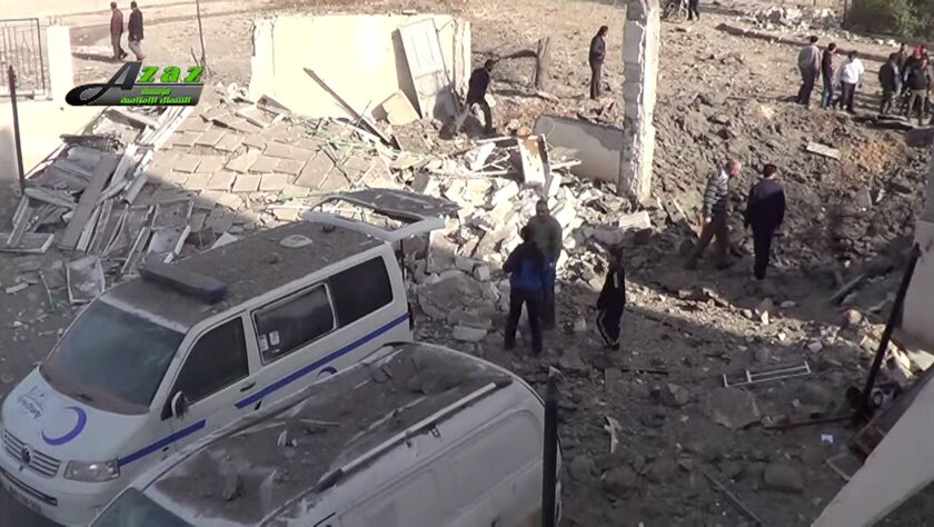 This image taken from video provided by the Syrian activist-based media group Azaz Media Center, which has-been verified and is consistent with other AP reporting, shows people gathered around destroyed vehicles in Azaz, Syria Syria, Monday, Feb. 15, 2016. Turkey says Kurdish forces have been expel