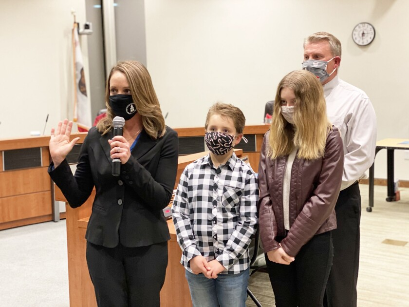 Newly-elected board member Cindy Sytsma is sworn in on Dec. 17, accompanied by her children Wyatt and Maddie and husband Jim.