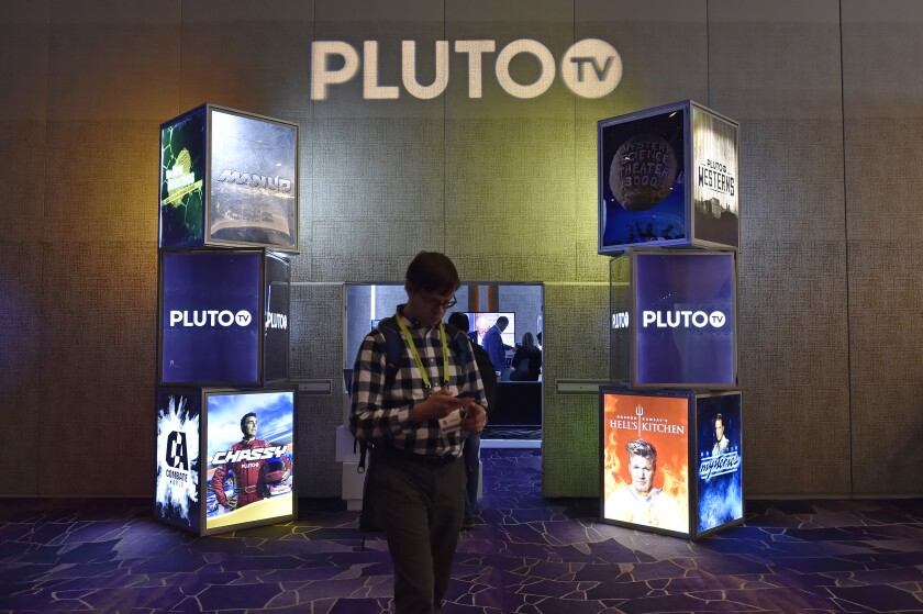 An attendee walks by the Pluto TV booth during CES 2019 at the Aria Resort & Casino in Las Vegas.
