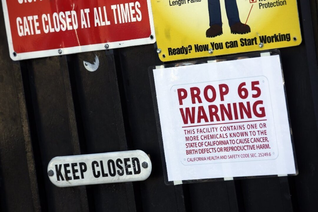 A Proposition 65 notice is one of several warning signs posted on a gate at Aerocraft Heat Treating in Paramount.